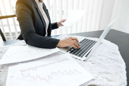 The hands of a female business brokerage are planning business investments by analyzing and calculating the stock market to find market profits.