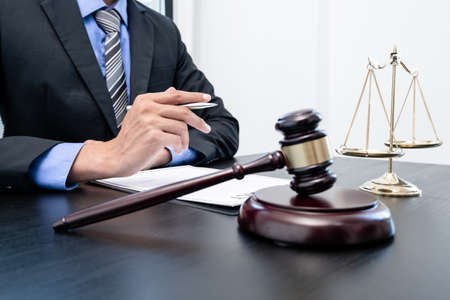 Professional male lawyers work at a law office There are scales, Scales of justice, judges gavel, and litigation documents. Concepts of law and justice.