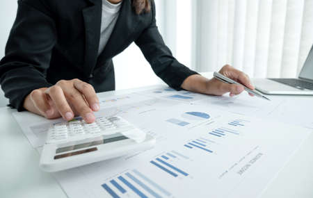 The hands of a male businesswoman use the calculator are analyzing and calculating the annual income and expenses in a financial graph that shows results To summarize balances overall in office.
