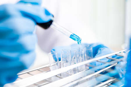 Medical scientists released a sample pipette into a test tube to analyze the virus in a chemical laboratory. Scientific research concepts.
