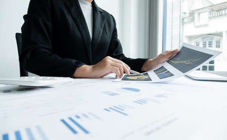 The hands of a male businesswoman are analyzing and calculating the annual income and expenses in a financial graph that shows results To summarize balances overall in office. Stock fotó