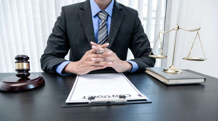 Professional male lawyers work at a law office There are scales, Scales of justice, judges gavel, and litigation documents. Concepts of law and justice. Stock Photo