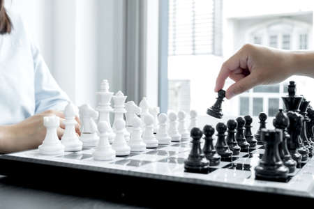 The hands of businessmen moving chess in chess competitions demonstrate leadership, followers, and strategic plans, business success building processes, and teamwork.