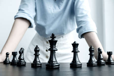 The hands of businesswomen moving chess in chess competitions demonstrate leadership, followers, and strategic plans, business success building processes, and teamwork.