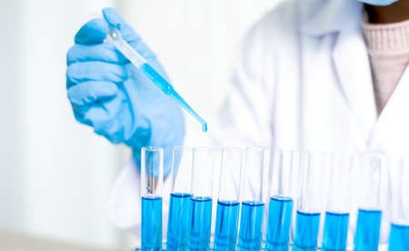 Medical scientists released a sample pipette into a test tube to analyze the virus in a chemical laboratory. Scientific research concepts. Stock fotó