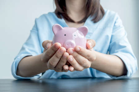 A woman's hand holds a piggy bank for saving into a growing business to succeed and save for retirement.