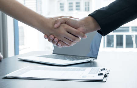 Friendly businessmen and executives shake hands after successful agreement with employment contracts, recruitment, and employment concepts.