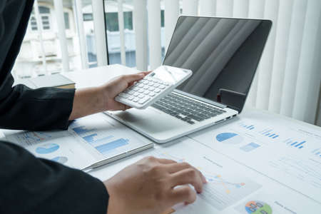 The hands of a male businesswoman use the calculator are analyzing and calculating the annual income and expenses in a financial graph that shows results To summarize balances overall in office. Stock fotó