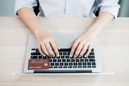 The businesswoman's hand is holding a credit card and using a laptop for online shopping and internet payment in the office.