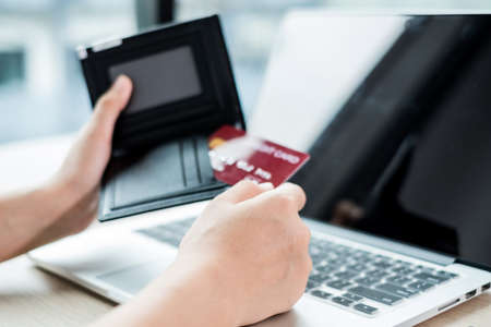The businesswoman's hand is holding a credit card and using a laptop for online shopping and internet payment in the office. Archivio Fotografico