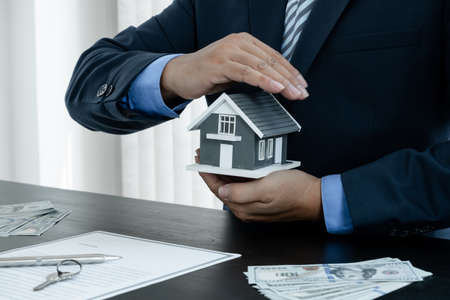 The house is covered by the hands of a real estate agent to protect the house for customers, homebuyers, insurance, ready give to with new owner. Home insurance sales concept.