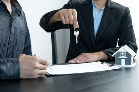 Real estate agent broker hand over the house key to the new owner after completing the signing according to agreement renting a house and buy house insurance officially completed.