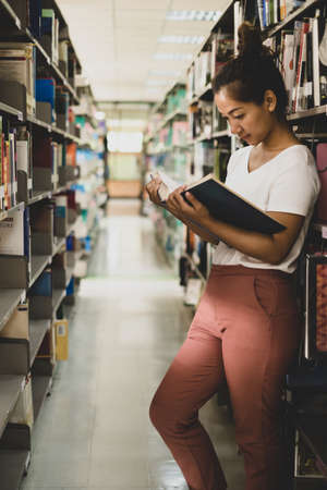 Young Asian women are searching for books and reading from the bookshelves in the college library to research and develop themselves in education. Stockfoto