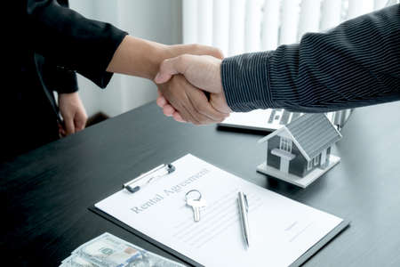 A real estate agent and clients shake hands after completing the home insurance contract negotiation and signing a formal contract. Rental and home insurance concepts.