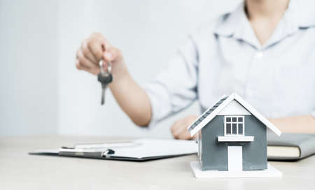 Real estate investment agents who hold keys with house designs and lease documents, make home purchase contracts, home insurance, and purchase approvals for clients.