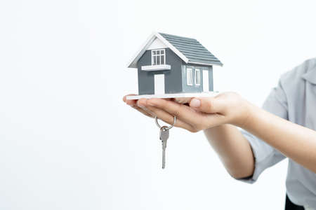 The hand of the real estate agent holding the house model and the keys Loan and home concept.