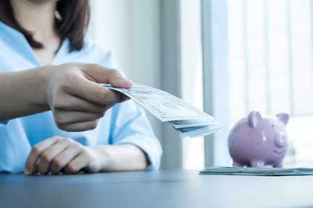 Women's hands hold dollars and put piggy banks to save money, expand successful businesses, and save for retirement.