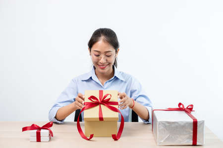 Asian women happy to open surprise box are stunned with excitement, joy and smile on holidays, Christmas, birthday or Valentine's Day concept.