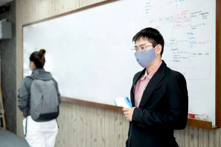 Back to school. Asian male teacher using thermometer temperature screening student for fever against the spread of COVID-19 Before entering the classroom. Virus protection concept.