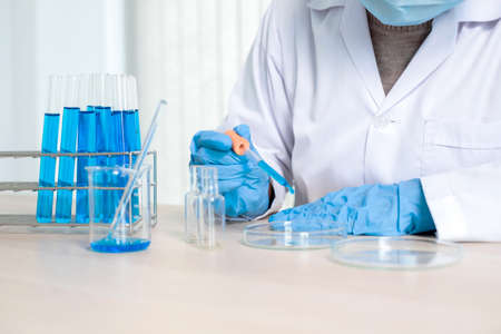 Medical scientists released a sample pipetted into test glassware to analyze the virus in a chemical laboratory. Scientific research concepts.