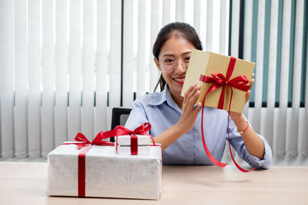 Asian woman holding a gift box Glad to be the giver of surprise with excitement, joy and smiles on the holidays, Christmas, birthdays or Valentine's Day concept.