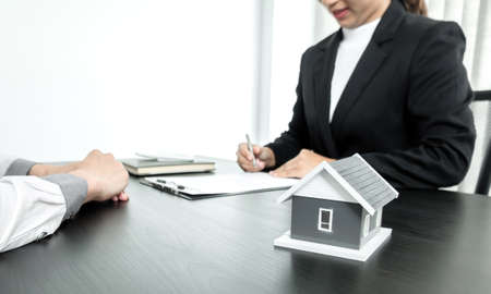 Real estate agents with house models are talking to customers about renting houses and buying home insurance. Rental and insurance concepts.