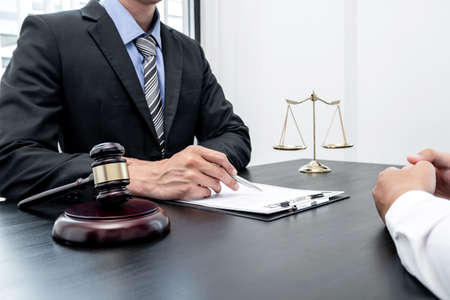 A male lawyer or a judge counseling clients about judicial justice and prosecution with scales, judges gavel, legal documents legal services concept. Imagens