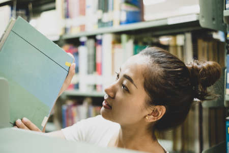Young Asian women are searching for books and reading books on the tables and aisles of the college libraries to research and develop their academic and education self. Stockfoto