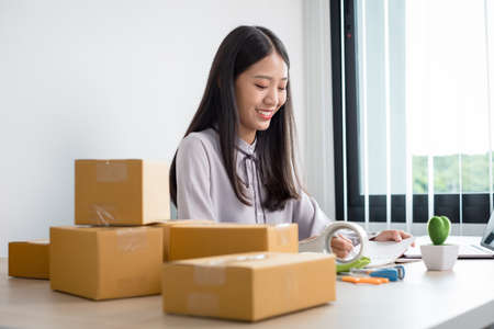 Young Asian woman business owner with many parcel boxes on the table happy online sales job, use your laptop, get an order from customers, take notes, and make arrangements for delivery by post.