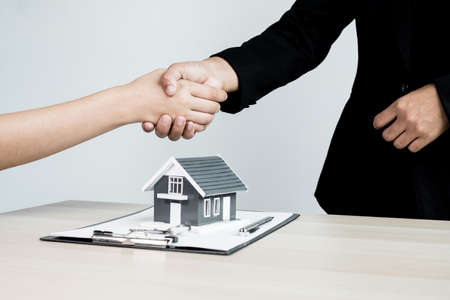Businessmen and brokers real estate agents shake hands after completing negotiations to buy houses insurance and sign contracts. Home insurance concept. 免版税图像