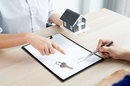 A real estate agent with rental homes and home insurance for clients to sign contracts under a formal home lease agreement. Home rental and insurance concept.