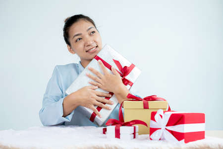 Asian woman holding a gift box Glad to be the giver of surprise with excitement, joy, and smiles on the holidays, Christmas, birthdays, or Valentine's Day concept. 版權商用圖片