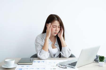 Working Asian women feel stressed, tired from work, migraine headaches from hard work while working at the office.