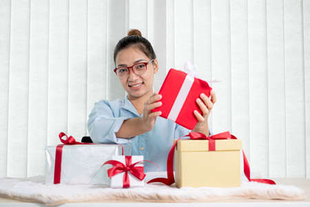 Asian woman holding a gift box Glad to be the giver of surprise with excitement, joy, and smiles on the holidays, Christmas, birthdays, or Valentine's Day concept.