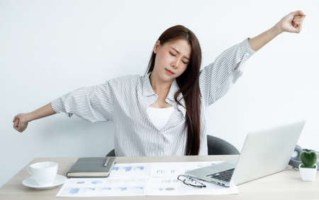 Asian women are tired from work on laptop sits in a chair stretching to relax and unwind while working hard at the office.