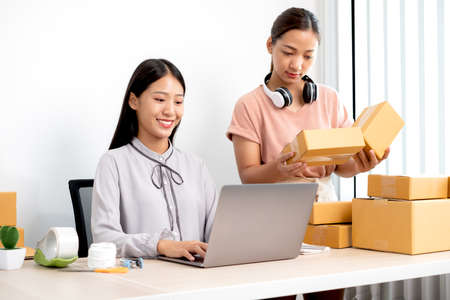 Asian woman business two people owner with many parcel boxes on the table happy online sales job, use your laptop, get an order from customers, take notes, and make arrangements for delivery by post.