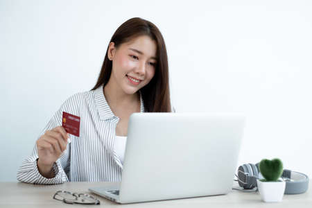 The Asian woman's hand is holding a credit card and using a laptop for online shopping and internet payment while sitting at a table indoors. Stock Photo
