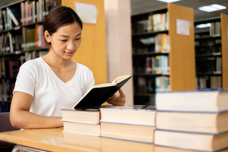 Young Asian women are searching for books and reading books on the tables and aisles of the college libraries to research and develop their academic and education self. 版權商用圖片