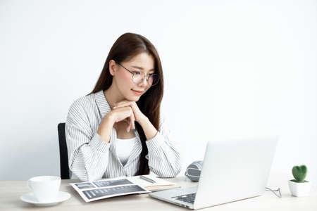 Video call, a young Asian woman wearing glasses communicates via online video long distance, looking at the digital laptop screen, happily greeted with a friend.