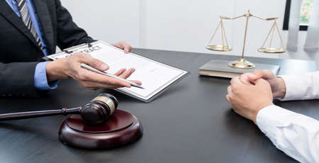 A male lawyer or a judge counseling clients about judicial justice and prosecution with scales, judges gavel, legal documents legal services concept.
