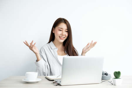 Video call, a young Asian woman communicates via online video long distance, looking at the digital laptop screen, happily greeted with a friend.