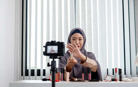 Muslim women making video beauty vlogger bloggers doing a cosmetic makeup tutorial vlog with brushes looking camera Save clips and share them on social media live via the internet Online. Stock fotó
