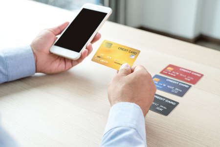 The businessman's hand is holding a credit card and using a smartphone for online shopping and internet payment in the office. Stock fotó