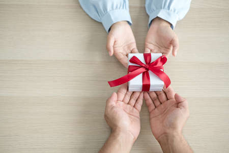 Gift box hand holding a gift box Glad to be the giver of surprise with excitement, the joy on the holidays, Christmas, birthdays, or Valentine's Day concept.