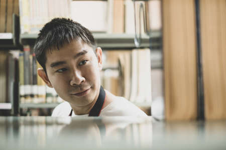 Young Asian men are in the college library to research and develop themselves in academia and education.