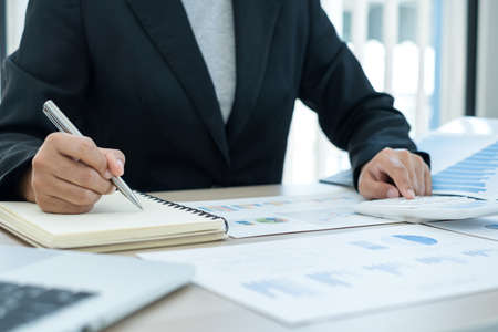 The businesswoman hand sits at their desks and calculates financial graphs showing the results of their investments planning the process of successful business growth.