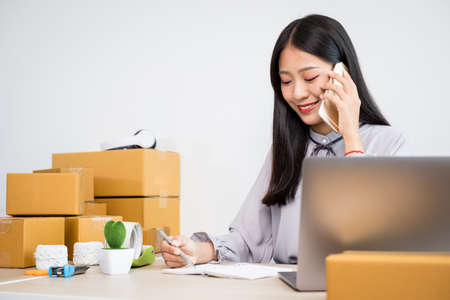 Young Asian woman business owner with many parcel boxes on the table happy online sales job, use your smartphone, get an order from customers, take notes, and make arrangements for delivery by post.