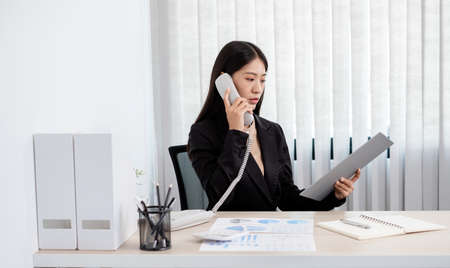 Asian businesswoman talking on the phone and working with a cheerful and happy smile while working at the office. Stock fotó