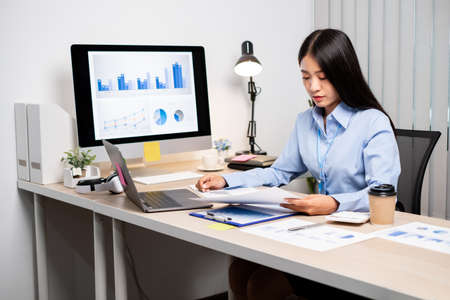 Asian women sit at their desks and calculate financial graphs showing results about their investments, plan a successful business growth process.