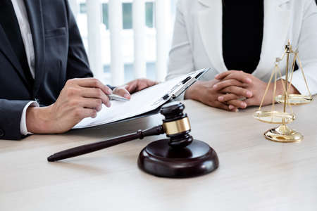 A male lawyer or a judge counseling clients about judicial justice and prosecution with scales, judges gavel, legal documents legal services concept. Stock fotó